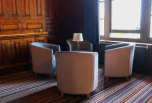 Four tub chairs and table by the lounge room window, YHA Swanage