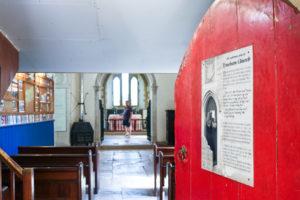 Church door opening onto pews at St Mary's, Tyneham