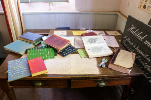 Books and schoolwork on display in younger children's area of the Tyneham schoolroom exhibition