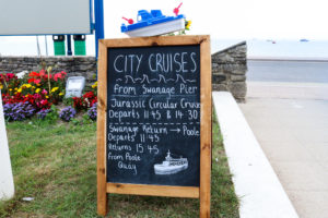 Depart and return times on a blackboard for Jurassic Circular Cruise from Swanage Pier