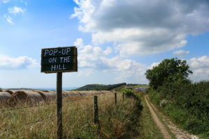 Pop-Up on the Hill sign with Dorset Coast and sea in the distance