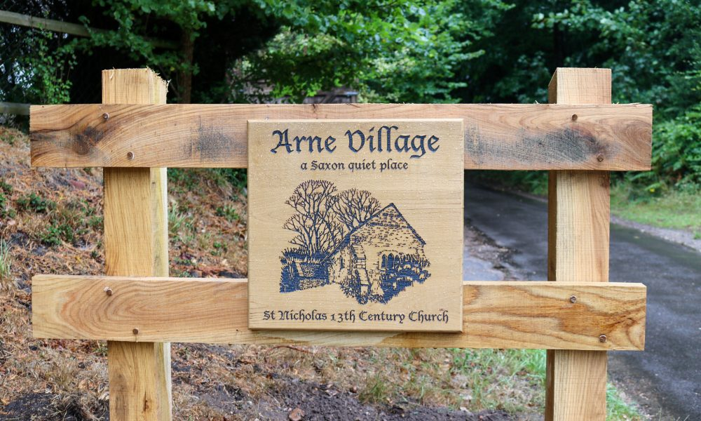 Arne village and St Nicholas church wooden sign