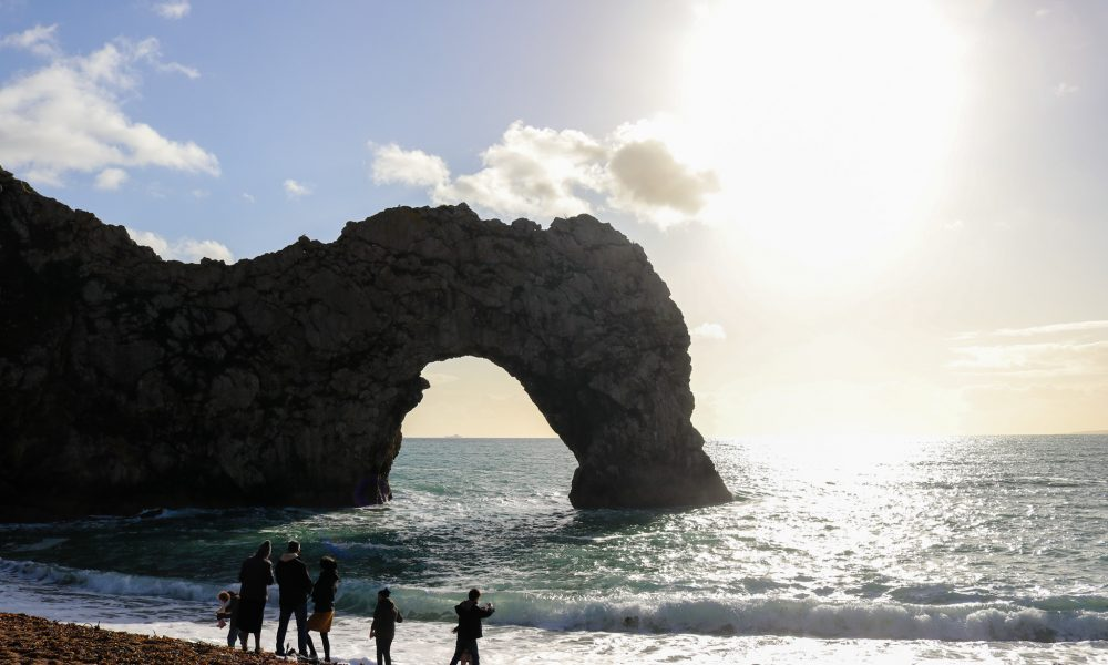 Family standing in front of Durdle Door arch