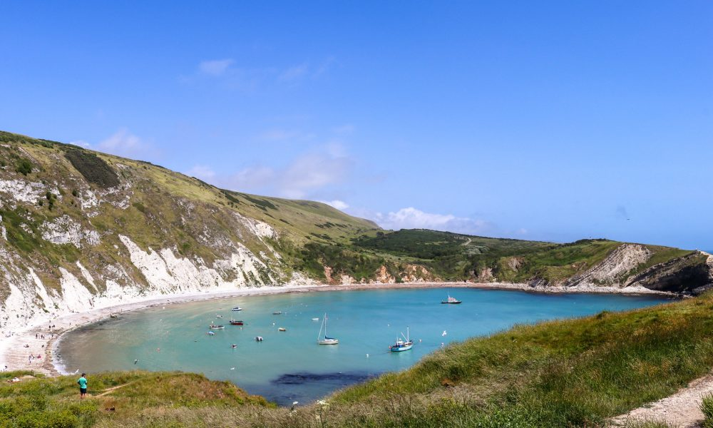 Lulworth Cove with boats and person