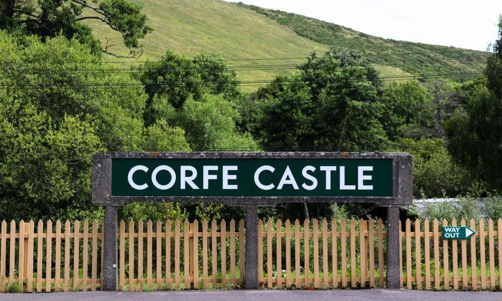 Corfe Castle railway station sign in front of Purbeck Hills