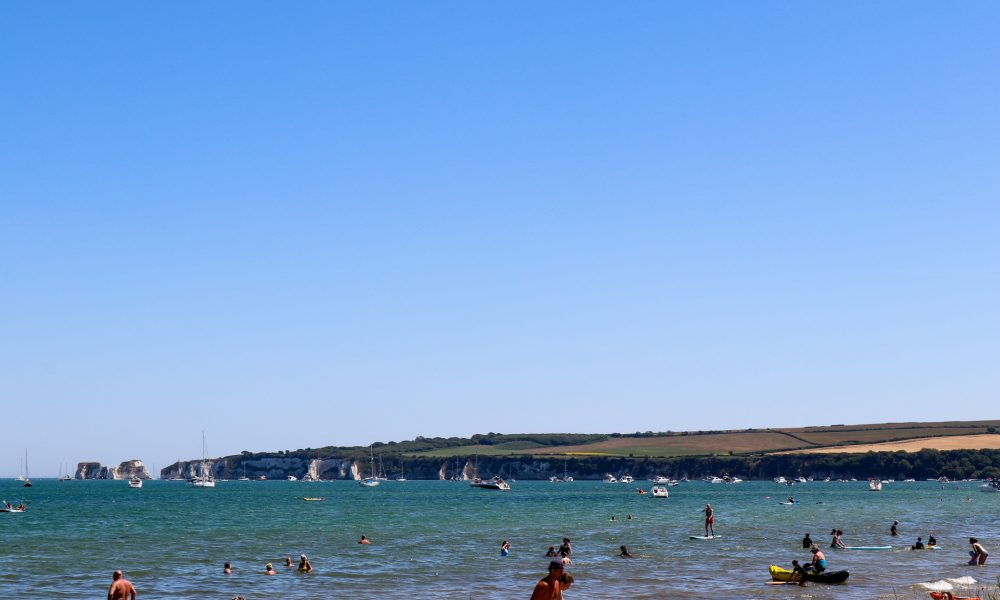 People on Knoll Beach with old Harry Rocks in background