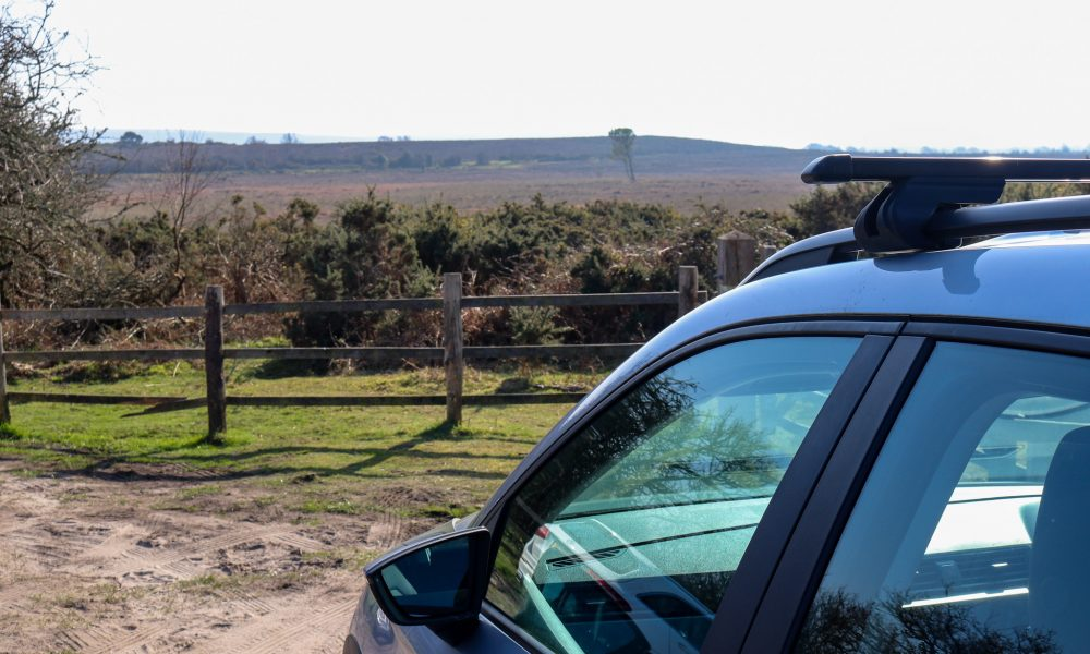 Car with roof rack facing toward Purbeck heathland and hills