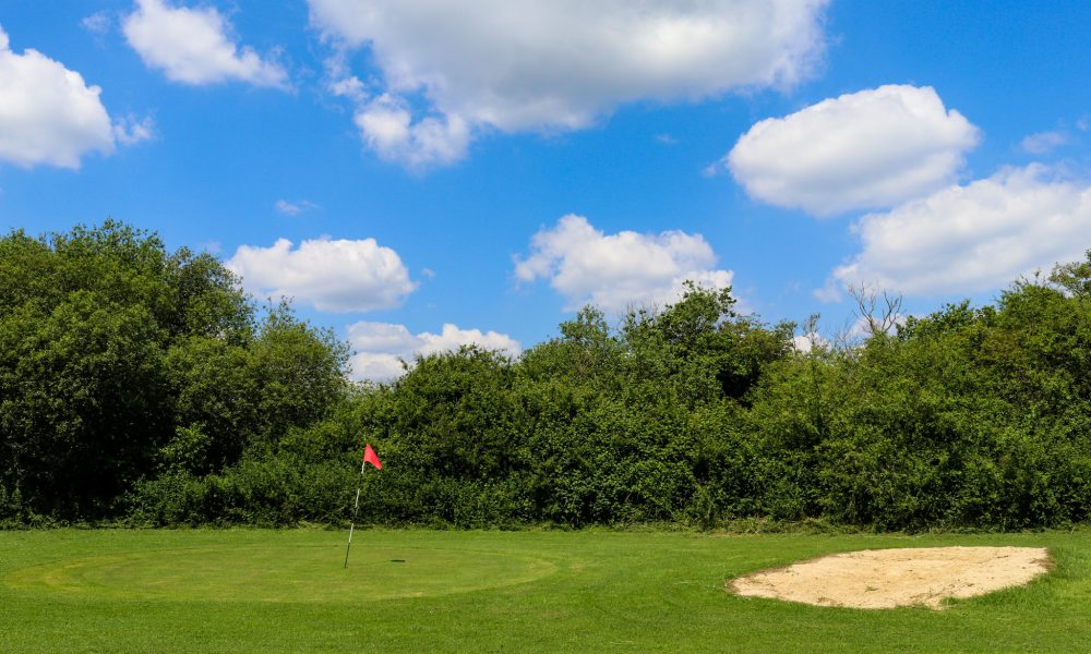 Bunker next to red flag at pitch & putt hole at Swanage Golf Games