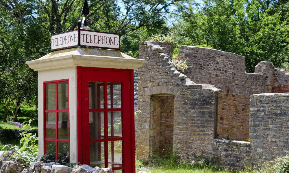 Old phone box in abandoned village Tyneham with ruined house in the background