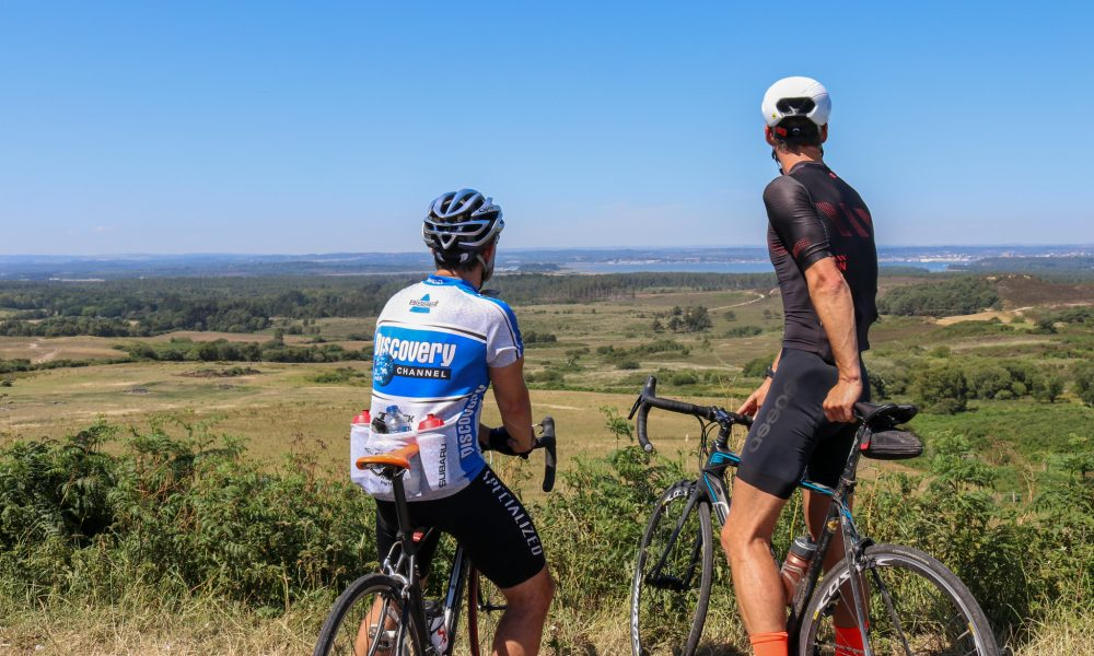 Two cyclists sitting on bikes looking at view over Studland from The Viewpoint near Corfe