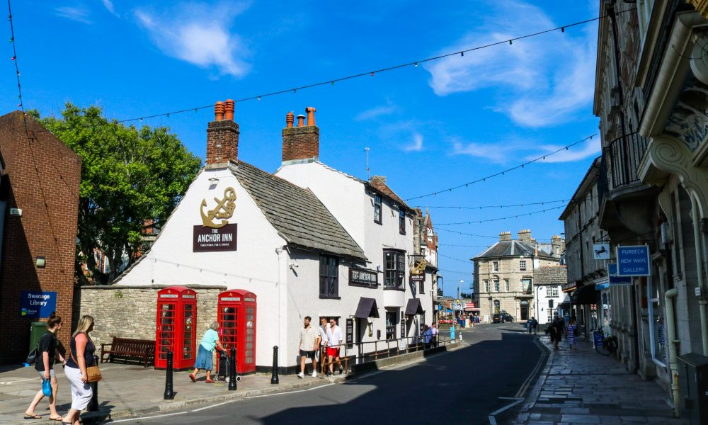 People walking past the Anchor Inn and Swanage library on a sunny day